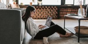 Frau mit Laptop im Wohnzimmer
